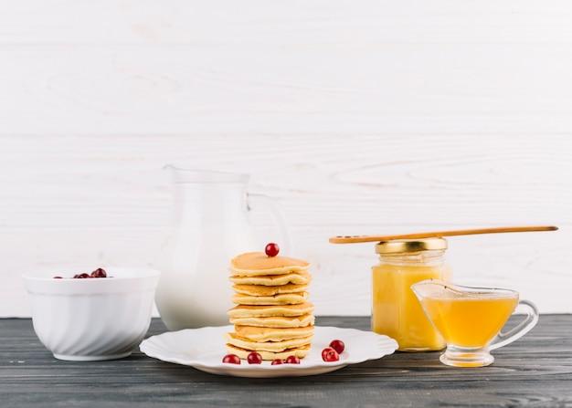 Gestapelt von den kleinen pfannkuchen mit beeren der roten johannisbeere und zitronenquark gegen weiße wand Kostenlose Fotos