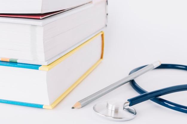 Gestapelte bücher; bleistift und stethoskop auf weiße fläche Kostenlose Fotos