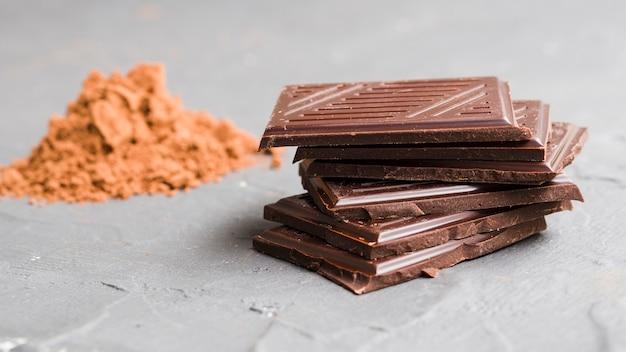 Gestapelte schokoladenstücke neben kakaopulver Kostenlose Fotos