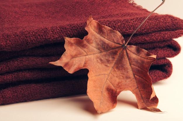 Gestapelter stapel von burgunder strickte plaid auf weißem hintergrund mit einem herbstblatt des ahorns Premium Fotos