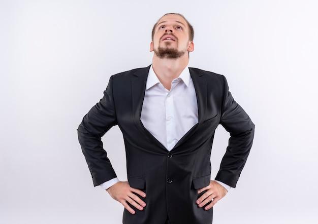 Gestörter hübscher geschäftsmann, der anzug trägt, der oben über weißem hintergrund steht Kostenlose Fotos