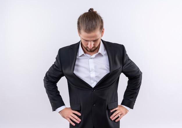 Gestörter hübscher geschäftsmann, der anzug trägt, der unten steht über weißem hintergrund Kostenlose Fotos