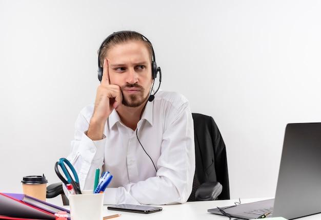 Gestörter hübscher geschäftsmann im weißen hemd und in den kopfhörern mit einem mikrofon, das einem kunden mit ernstem gesicht zuhört, der am tisch in offise über weißem hintergrund sitzt Kostenlose Fotos