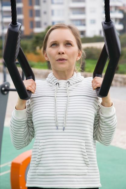 Gestrafftes sportliches mädchen, das mit aufhängungsbügeln ausarbeitet Kostenlose Fotos