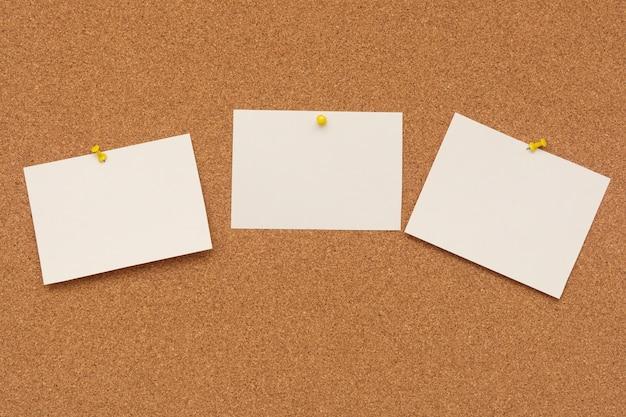 Gestreifte briefpapiere mit stecknadeln vom korkbrett Premium Fotos