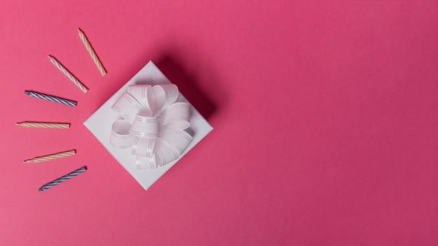 Gestreifte kerzen und geschenkbox auf rosa hintergrund Kostenlose Fotos