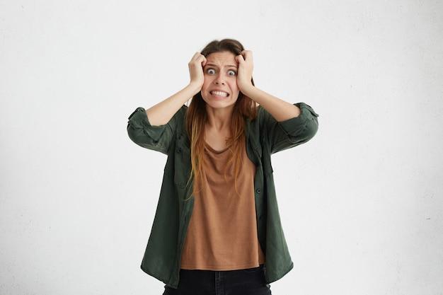 Gestresste ängstliche junge, lässig gekleidete frau, die sich die haare ausreißt, während sie probleme hat, spannung und stress verspürt, druck nicht aushält, zähne zusammenbeißt und die augen herausspringt. Kostenlose Fotos