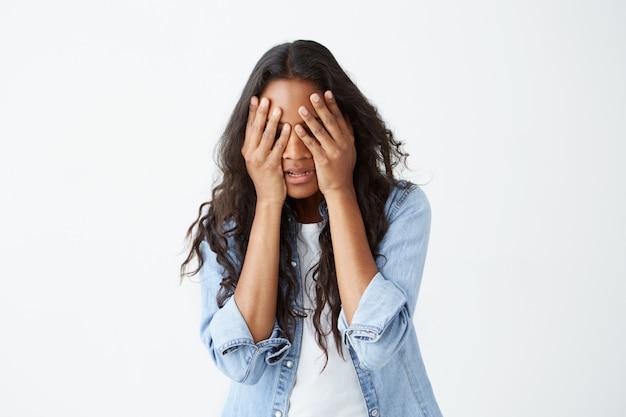 Gestresste afroamerikanische frau mit langen, welligen haaren, lässig gekleidet, verärgert, die hände auf dem kopf haltend und ihr gesicht verzweifelt versteckt, nachdem sie schlechte nachrichten gehört hatte. Kostenlose Fotos