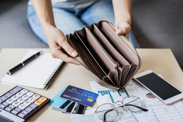 Gestresste junge frau öffnet ihre leere brieftasche und berechnet die ausgaben zu hause Premium Fotos