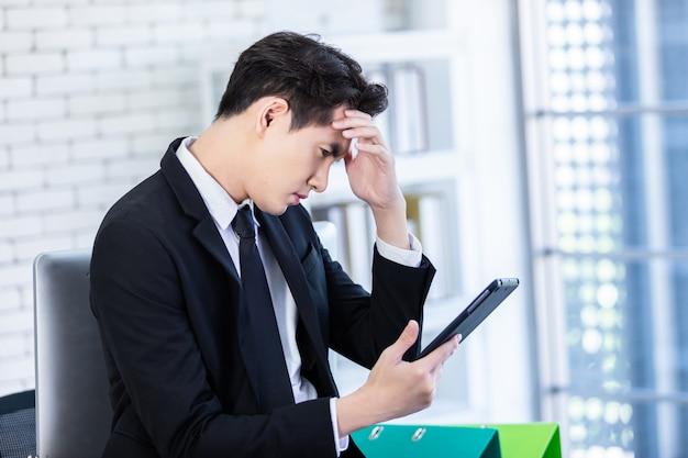 Gestresster mann, der mit einer tablette arbeitet Premium Fotos