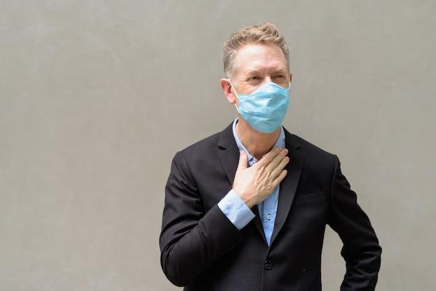 Gestresster reifer geschäftsmann mit maske, die draußen krank wird Premium Fotos