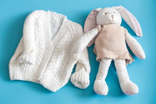 Gestrickte babykleidung und accessoires auf blauem grund. Kostenlose Fotos