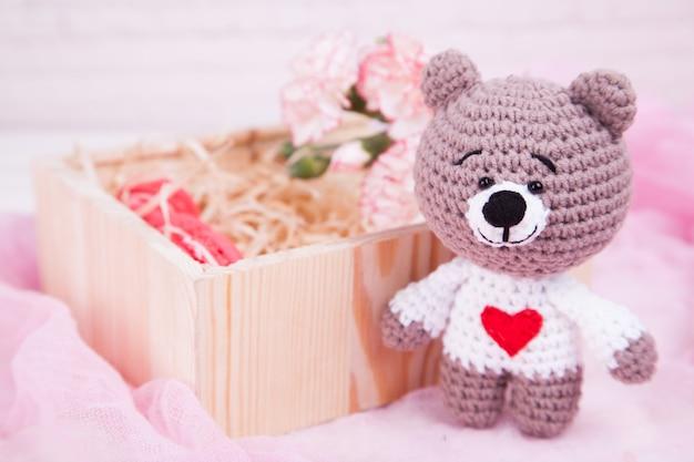 Gestrickte katze mit einem herzen und rosen. valentinstag dekor. gestricktes spielzeug, amigurumi. Premium Fotos