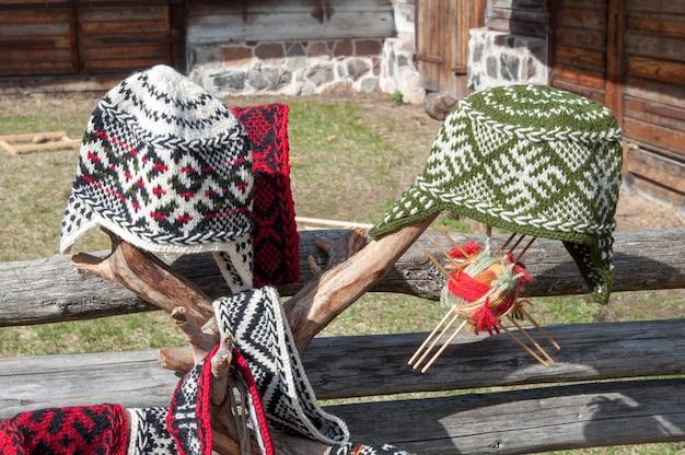Gestrickte lettische mütze mit verzierung auf holzzaun draußen Premium Fotos