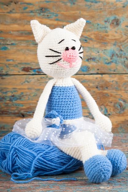 Gestrickte weiße katze in einem blauen kleid auf einem alten hölzernen hintergrund. handarbeit, kunsthandwerk. amigurumi Premium Fotos
