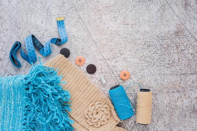 Gestrickter schal; maßband; taste; spulen auf strukturiertem hintergrund Kostenlose Fotos