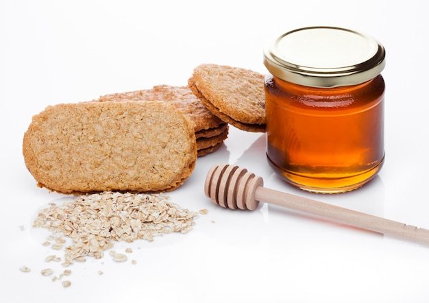 Gesunde biofrühstückskornkekse mit honig und rohem haferbrei auf weißem hintergrund Premium Fotos