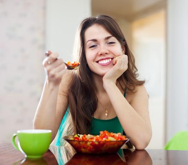 Gesunde frau, die veggiesalat isst Kostenlose Fotos