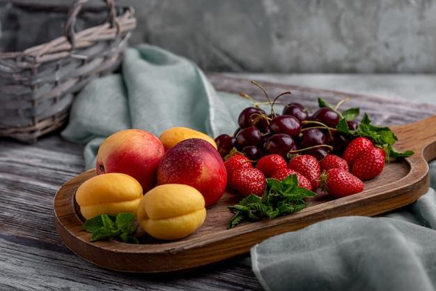 Gesunde fruchtservierplatte, erdbeeren, äpfel, pfirsiche, aprikosen auf einem dunkelgrauen holztisch, draufsicht, nahaufnahme, selektiver fokus. Premium Fotos