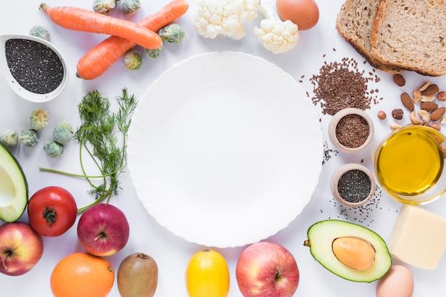 Gesunde früchte; gemüse; trockenfrüchte; brot; samen und käse; ei; öl; mit leerer platte über weißem hintergrund Kostenlose Fotos