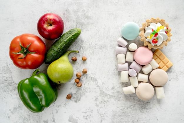 Gesunde früchte; gemüse und haselnüsse gegenüber dem hintergrund mit einer vielzahl von desserts Kostenlose Fotos