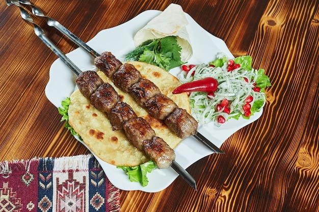 Gesunde gegrillte magere gewürfelte schweinefleischspiesse, serviert mit einer maistortilla und frischem salat- und tomatensalat, nahaufnahme Premium Fotos