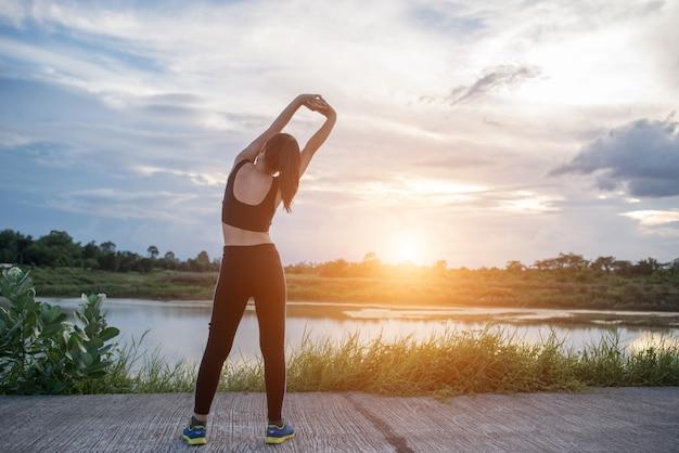 Gesunde junge frau, die draußen training vor trainingssitzung am park aufwärmt. Kostenlose Fotos