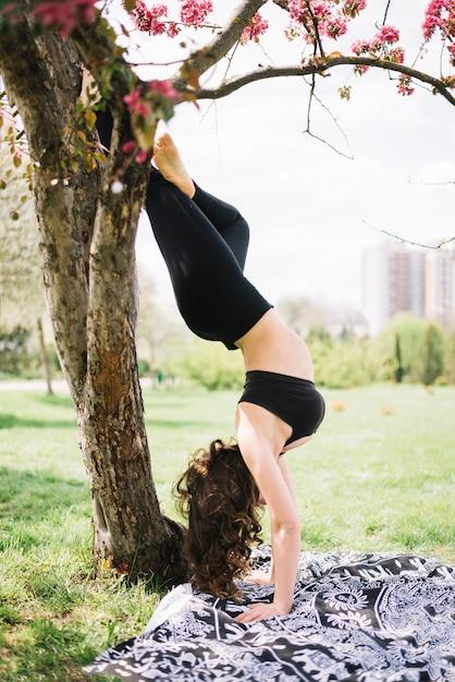 Gesunde junge frau, die handstandübung im garten tut Kostenlose Fotos