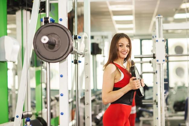 Gesunde junge frau mit barbell, in einem roten sportanzug, werfend in der turnhalle auf Premium Fotos
