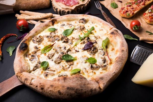 Gesunde köstliche pilzkäsepizza umgeben mit italienischen lebensmittelinhaltsstoffen Kostenlose Fotos