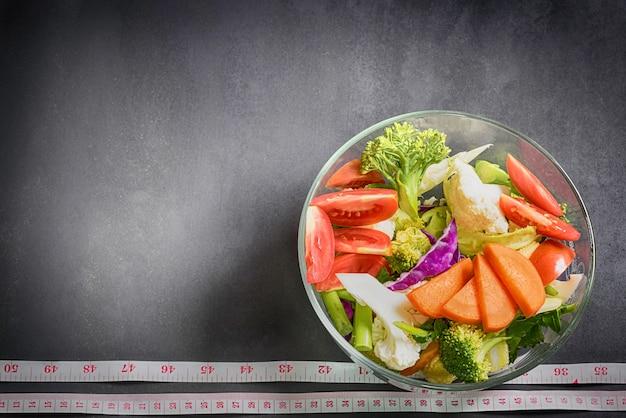 Gesunde lebensmittel sind auf dem tisch, frischgemüsesalat in einem glasbogen Premium Fotos