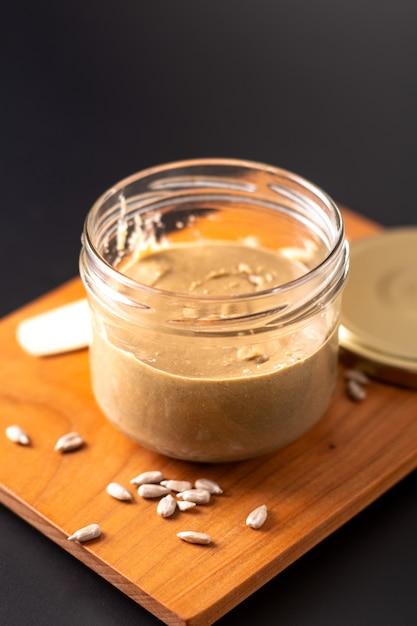 Gesunde lebensmittelkonzept homemake-sonnenblumenbutter im glasgefäß durch organische sonnenblumensamen auf schwarzem hintergrund Premium Fotos