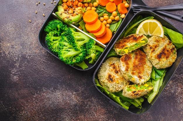 Gesunde mahlzeitvorbereitungsbehälter mit grünen burgern, brokkoli, kichererbsen und salat. Premium Fotos