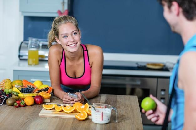 Gesunde paare, die frucht in der küche sprechen und halten Premium Fotos