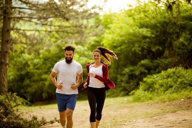 Gesunde passform und sportliche paare, die in natur laufen Premium Fotos