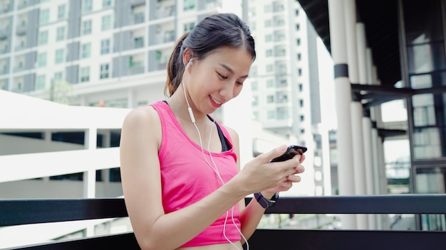 Gesunde schöne junge asiatische athletenfrau, die smartphone für verwendet, hören musik beim laufen Kostenlose Fotos