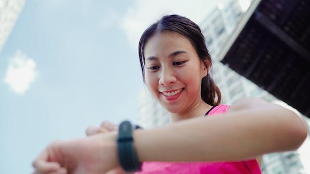 Gesunde schöne junge asiatische athletenfraueneinstellung und überprüfungsfortschritt, der herzfrequenzmonitor schaut Kostenlose Fotos