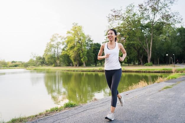 Gesunde schöne junge asiatische läuferfrau beim sportkleidungsbetrieb und -rütteln Kostenlose Fotos