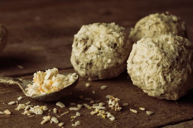 Gesunde schokoladenenergie beißt mit nüssen, datteln, kokosflocken auf einem holztisch. hausgemachte vegetarische glutenfreie gesunde snacks. rustikales tonen. Premium Fotos
