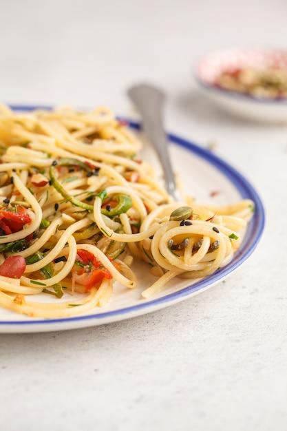 Gesunde vegane teigwaren mit zucchini, tomaten und nüssen. Premium Fotos