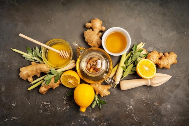 Gesunden antioxidans- und entzündungshemmenden ingwertee mit frischem ingwer, zitronengras, salbei, honig und zitrone auf dunklem hintergrund mit kopienraum machen. ansicht von oben. Premium Fotos