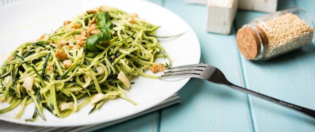 Gesunder grüner salat der hohen ansicht und zerquetschte samen in den gläsern Kostenlose Fotos