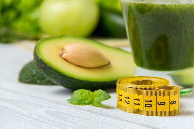 Gesunder grüner smoothie mit bestandteilen auf weißem holz Premium Fotos