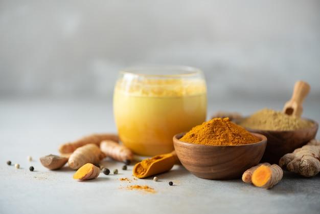 Gesunder kurkuma latte des strengen vegetariers oder goldene milch, gelbwurzwurzel, ingwerpulver, schwarzer pfeffer über grauem konkretem hintergrund. Premium Fotos