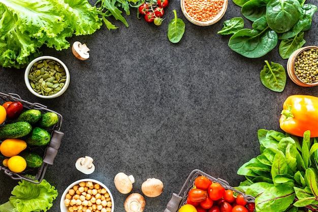 Gesunder lebensmittelhintergrund. herbstfrisches gemüse auf dunklem steintisch mit kopienraum, draufsicht Premium Fotos