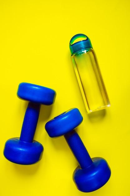Gesunder lebensstil, gesunde gewohnheiten. detoxwasser, obstsalat, sportausrüstungsdummköpfe auf blauem kopienraum der draufsicht des hintergrundes Premium Fotos