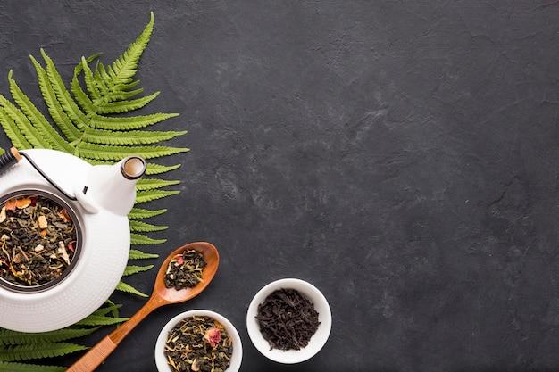 Gesunder organischer tee mit trockenem kraut und farn verlässt auf schwarzer oberfläche Kostenlose Fotos