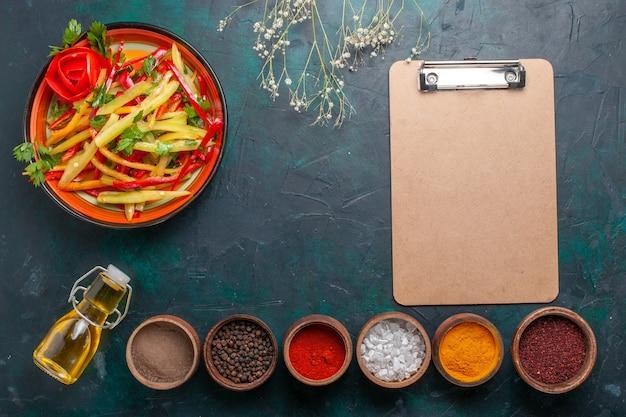 Gesunder salat der geschnittenen paprika der draufsicht mit olivenöl und gewürzen auf dunkelblauem hintergrund Kostenlose Fotos