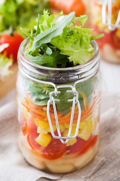 Gesunder salat im weckglas mit weißen bohnen, tomaten, zwiebel, mais und kopfsalat auf holztisch Premium Fotos