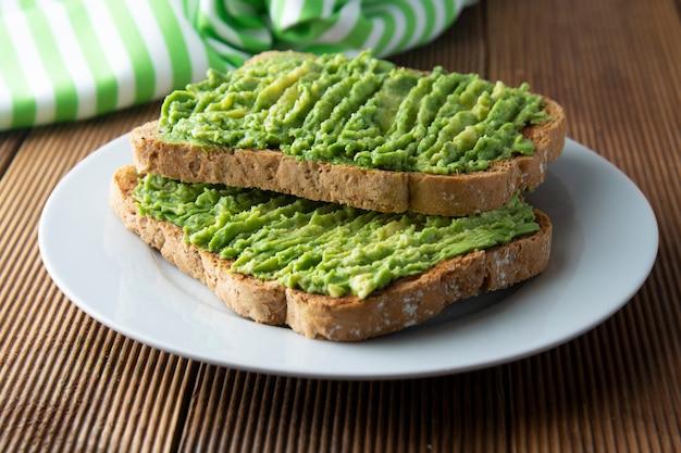 Gesundes avocadosandwich, toastbrot. mushed avocado-nudeln. guacamole. Premium Fotos